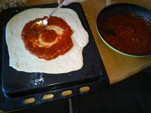 למרוח רוטב עגבניות בצורה אחידה עד כמה שאפשר על כל הבצק