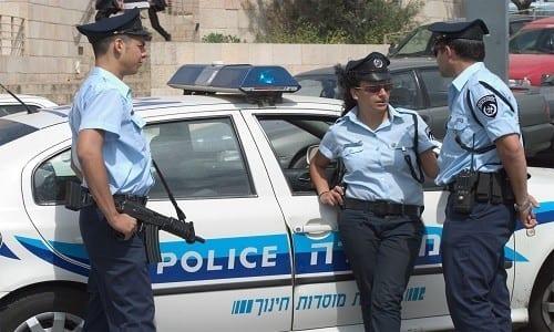שלושה שוטרים בישראל נשענים על ניידת