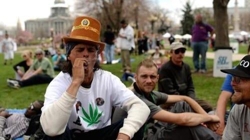 גבר עם חולצה עם הדפס עלה גראס מעשן קנאביס על המדשאה מול הבית הלבן