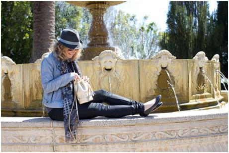 אישה בלונדינית יושבת ליד מזרקה ומחזיקה תיק של אנאביס
