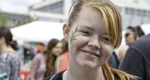 נערה מחייכת עם עלה מריחואנה