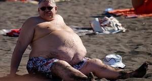 איש שמן סובל מהשמנת יתר יושב על חוף הים