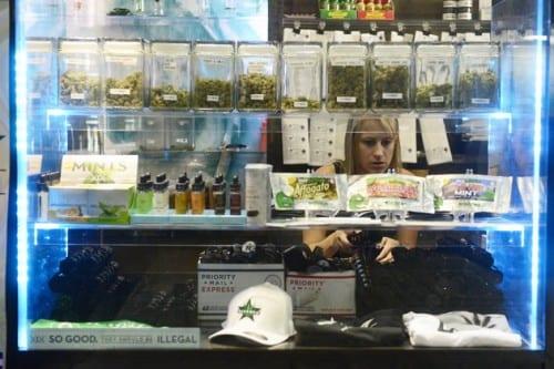 אישה בוחרת קנאביס לרכישה מתוך חלון תצוגה בחנות קנאביס בקולורדו