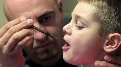 אבא נותן לבנו החולה שמן קנאביס במזרק