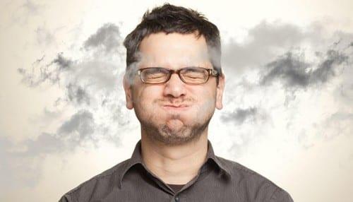 גבר עוצר את נשימתו ומסביבו ענני עשן על רקע לבן