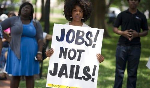"""אישה מחזיקה שלט """"תנו לנו עבודות, לא כלא"""""""