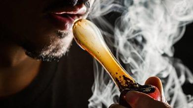גבר מעשן קנאביס במקטרת זכוכית על רקע שחור