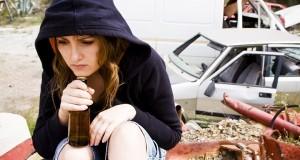 נערה צעירה מחזיקה בקבוק בירה