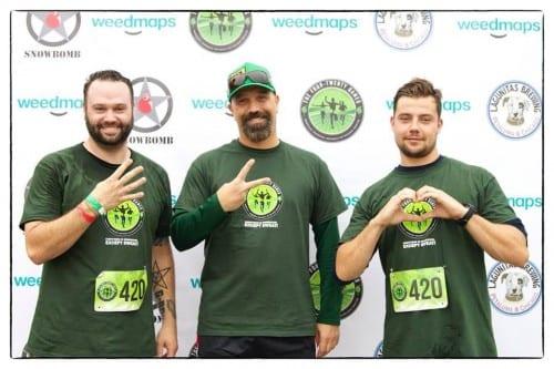ג'ים מק'אלפיין (במרכז) מייסד 420Games ושני רצים על רקע קיר עיתונאים לאחר התחרות