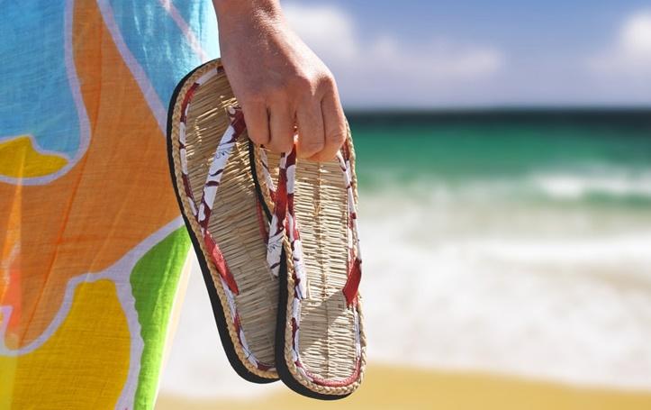 אשה מחזיקה כפכפים בחוף