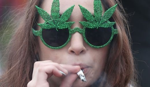 אשה מעשנת ג'וינט עם משקפי קנאביס