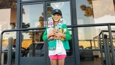 ילדת צופים מוכרת עוגיות מול חנות מריחואנה
