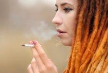 צעירה עם ראסטות מעשנת ג'וינט קנאביס