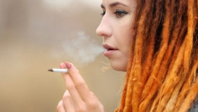 A young woman with dreadlocks smoking a joint of Cannabis